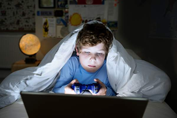 Child staying up late playing video games.
