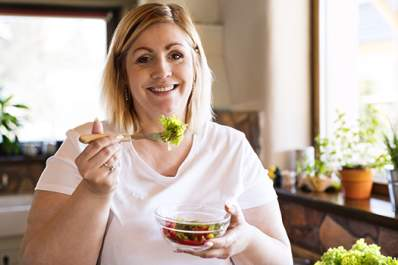 Happy overweight woman eating a salad in the kitchen.