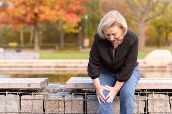 woman grabbing her knee, knee joint pain while sitting in park.