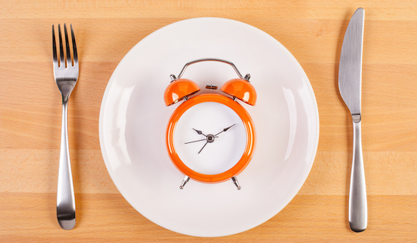 Alarm clock on dinner plate, fasting concept.
