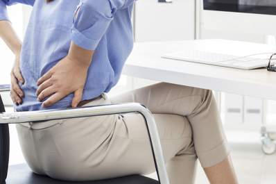 Woman with low back pain sitting in chair at work.