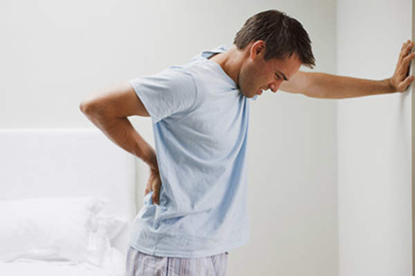 Man with back pain leaning against a wall.