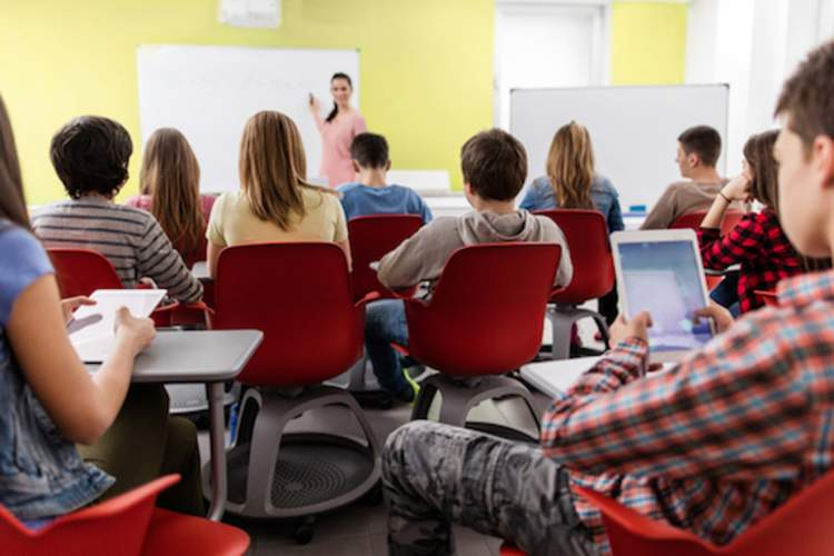 Teacher addressing students in high school classroom.