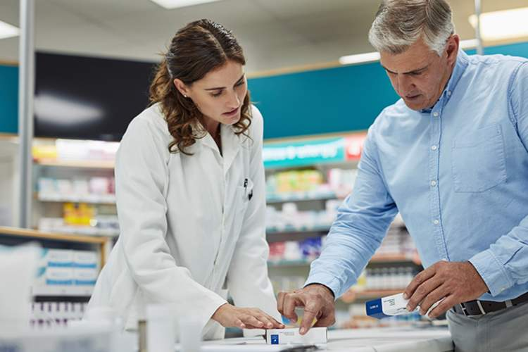Man discussing medications with his pharmacist.