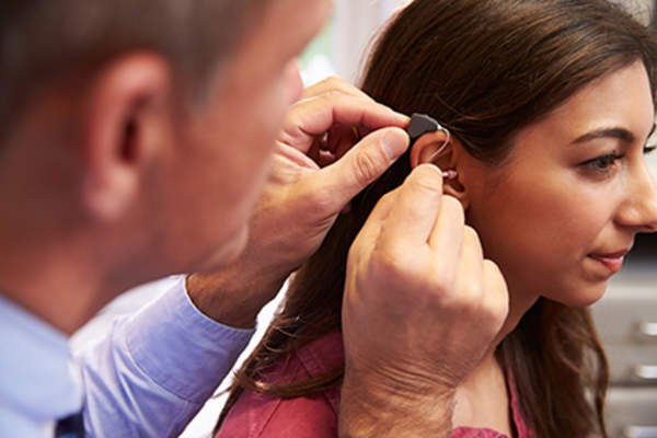 Doctor fitting a patient for a hearing aid.