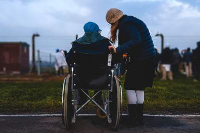 Elderly man in wheelchair and young woman, from behind