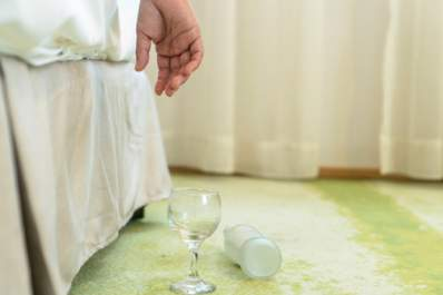 Hand hanging off of bed with empty glass and bottle on floor.