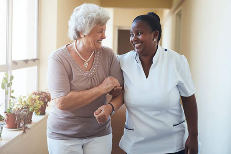 Smiling home caregiver and senior woman walking together