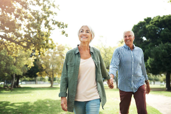 healthy older couple walking in park