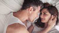 Couple looking at each other lovingly in bed.