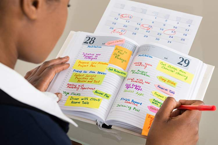 Businesswoman writing in her schedule.