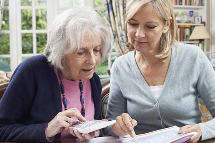 woman helping elderly mother with finances image