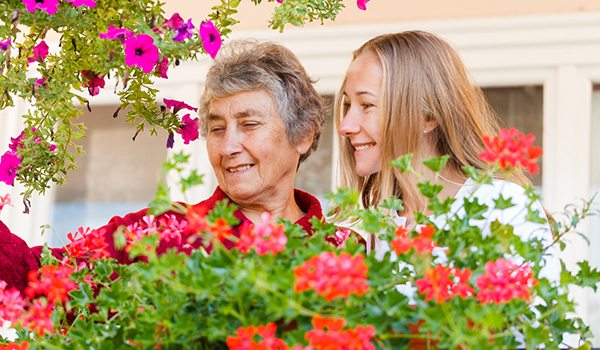 Younger woman and senior woman tending to hanging flower baskets.