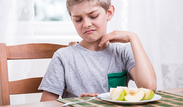 Boy refusing to eat apples.