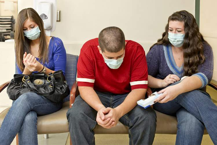 Young people with flu in hospital waiting room.