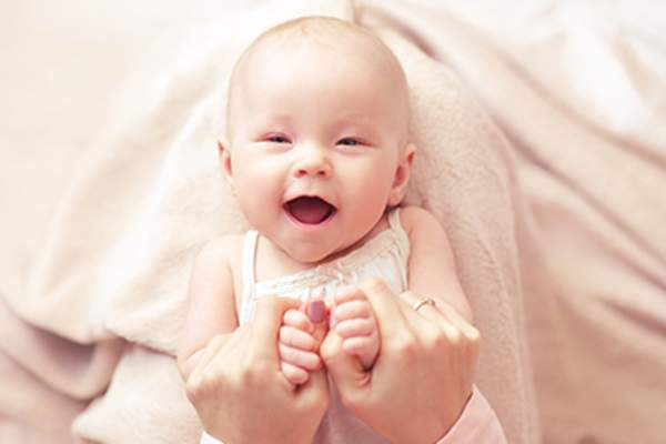 Smiling baby close up with mother's hands.