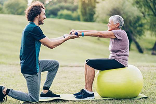 Senior woman on exercise ball in park with exercise instructor.