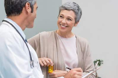 Smiling adult woman talking to doctor.