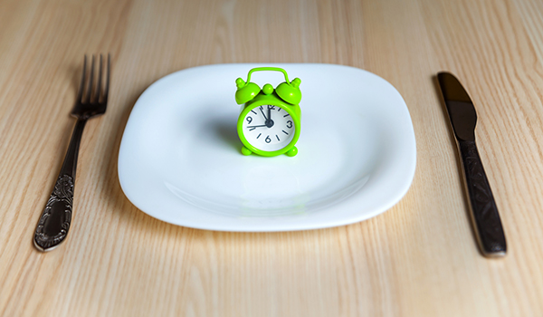 Fasting, alarm clock on a plate concept
