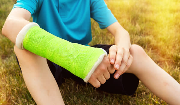 Young boy with a fractured arm wearing a cast.