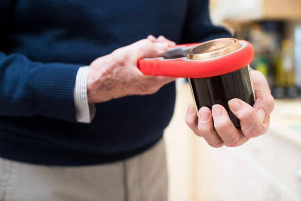 Close Up Of Senior Man Taking Lid Off Jar With Kitchen Aid