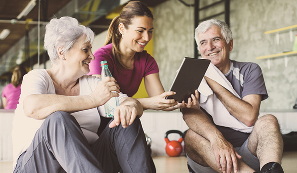 Smiling senior couple with fitness trainer.