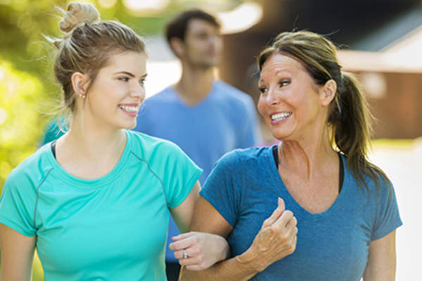 Smiling mother and teen daughter walking with arms linked.
