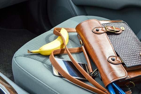 Banana and purse on front seat of car.
