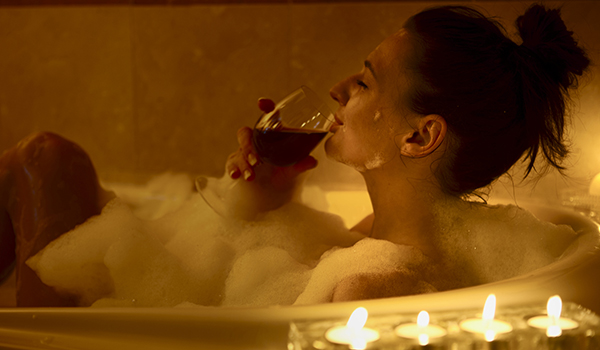 Woman relaxing and drinking wine in the bath.