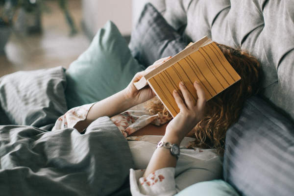tired woman covering face with book in bed
