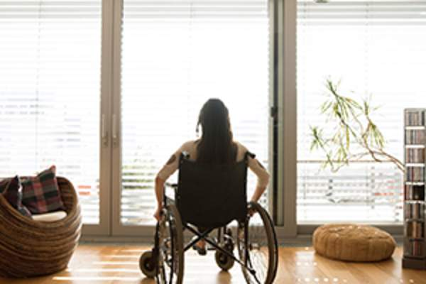 Woman in wheelchair looking out a wide sunny window.