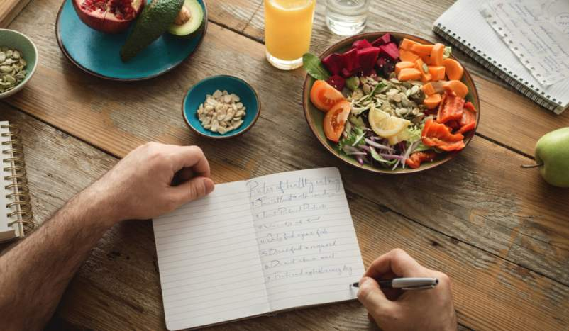 man writing in food diary