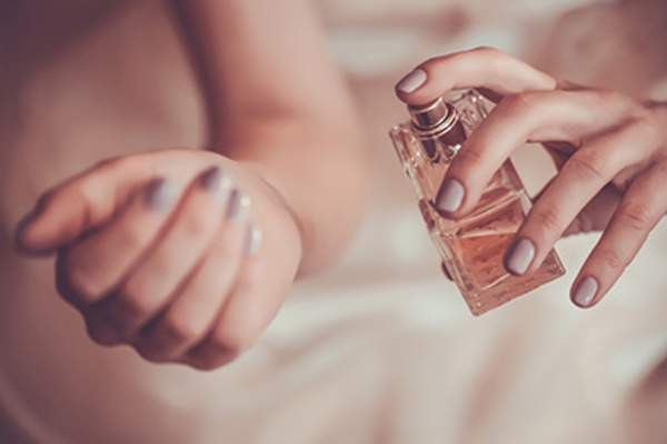 Woman spraying perfume on wrist.