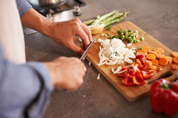 man cutting up veggies image