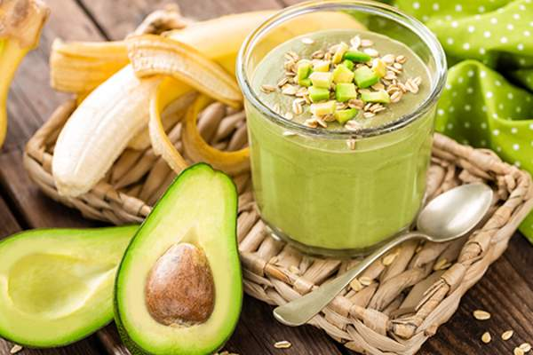 Avocado and banana smoothie with oats with ingredients in glass jar on wooden background