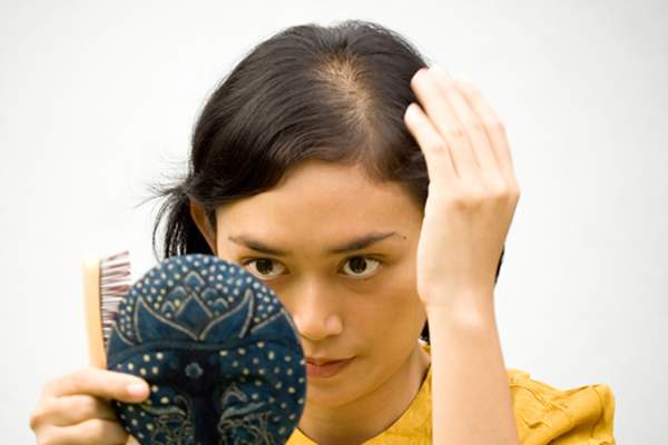 Woman looking in mirror worried about hair loss image.