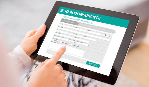 woman on tablet looking to buy health insurance