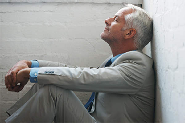 Man sitting against a wall on the floor.