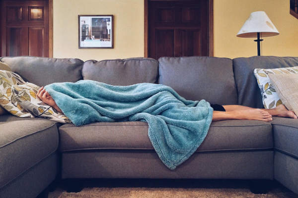 woman sick under blanket on couch