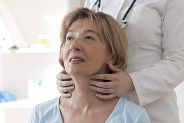 Doctor examining patient's thyroid.