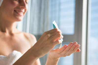 Woman squeezing ointment onto her hands after a shower.