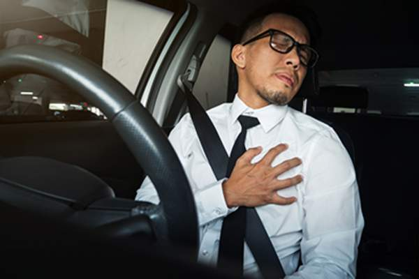 Man having chest pain while driving.