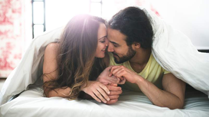 Young couple snuggling and kissing under the comforter on bed.