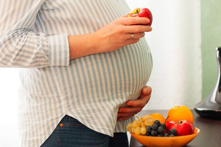 Pregnant woman holding an apple.