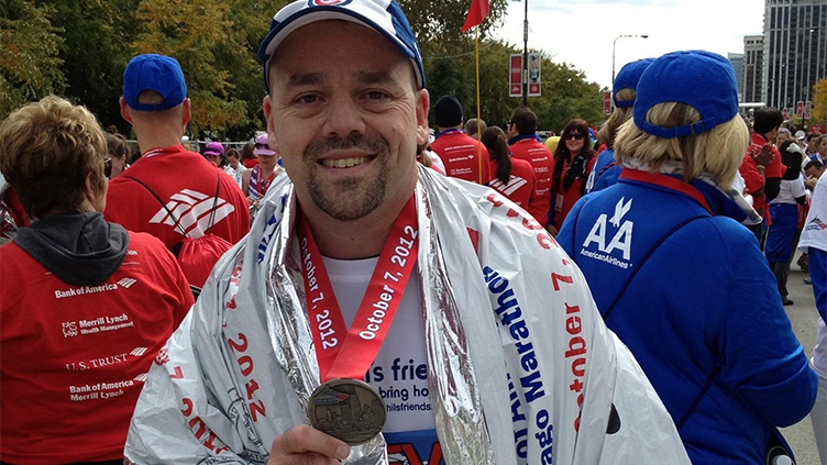 Steve DeLuca at end of marathon with medal in hand.