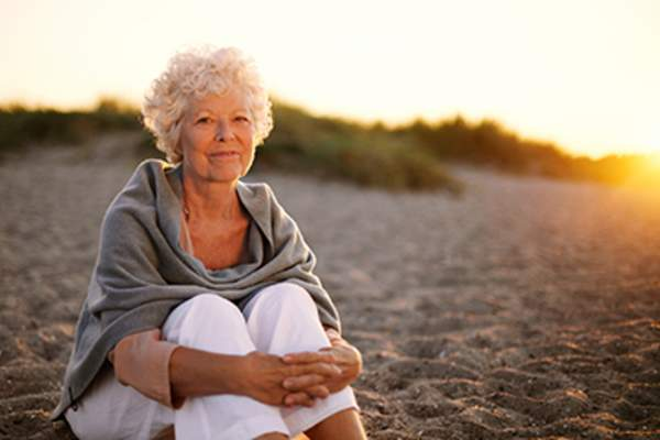 Senior woman sitting on a beach.