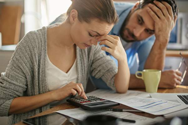 Stressed couple paying bills.