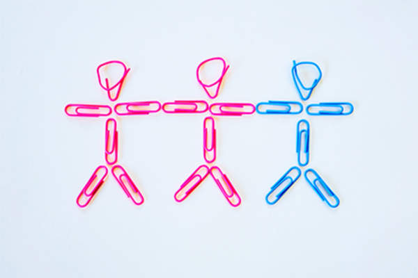 Two female, one male stick figures made from paper clips.