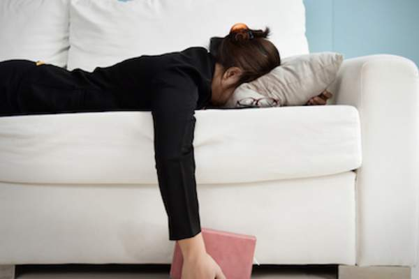 Fatigued woman face down on couch.