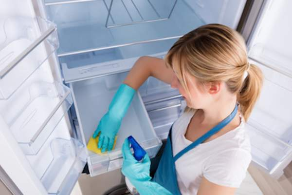 Woman deep cleaning refrigerator.